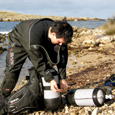 Student of underwater archeology preparing his equipment  to dive in Sanisera